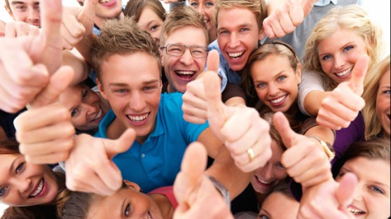 Group of successful students giving the thumbs up